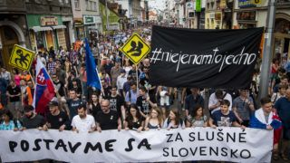 """Protesters hold a banner reading """"Stand up for decent Slovakia"""" during a protest in Bratislava,  Slovakia, on May 4, 2018.  Journalists firings at the public TV and radio broadcaster RTVS, sparked protests across Slovakia  again, nine weeks after the murder of journalist Jan Kuciak and his fiancee.  / AFP PHOTO / VLADIMIR SIMICEK"""