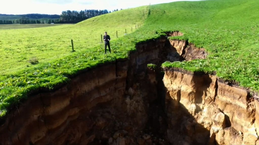 """This frame grab from TVNZ video footage taken on May 2, 2018 and released to AFP on May 7 shows a sinkhole that appeared on a dairy farm near Rotorua on New Zealand's North Island. A new sinkhole on a North Island farm as deep as four double-decker buses and almost the length of two football fields has grabbed the attention of New Zealand volcanologists. / AFP PHOTO / TVNZ / - /  - New Zealand OUT / RESTRICTED TO EDITORIAL USE - MANDATORY CREDIT """"AFP PHOTO / TVNZ"""" - NO MARKETING NO ADVERTISING CAMPAIGNS - DISTRIBUTED AS A SERVICE TO CLIENTS == NO ARCHIVE"""
