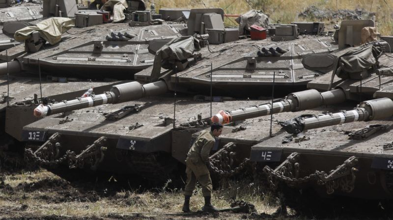 Israeli Merkava tanks and soldiers are seen in a deployment area near the Syrian border in the Israel-annexed Golan Heights on May 10, 2018. Israel's army said today it had carried out widespread raids against Iranian targets in Syria overnight after rocket fire towards its forces it blamed on Iran, marking a sharp escalation between the two enemies. Israel carried out the raids after it said around 20 rockets, either Fajr or Grad type, were fired from Syria at its forces in the occupied Golan Heights at around midnight. / AFP PHOTO / MENAHEM KAHANA