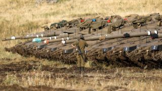 An Israeli soldier stands next to Merkava Mark IV tanks in a deployment area near the Syrian border in the Israel-annexed Golan Heights on May 10, 2018. Israel's army said today it had carried out widespread raids against Iranian targets in Syria overnight after rocket fire towards its forces it blamed on Iran, marking a sharp escalation between the two enemies. Israel carried out the raids after it said around 20 rockets, either Fajr or Grad type, were fired from Syria at its forces in the occupied Golan Heights at around midnight. / AFP PHOTO / MENAHEM KAHANA