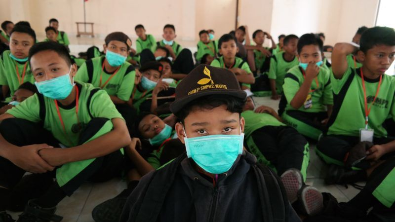 """Indonesian schoolchildren wear masks at school after mount Merapi erupted, in Sleman on May 11, 2018. Indonesian villagers living in the shadow of one of the world's most active volcanoes fled to safety on May 11 as the crater blew its top, sending a cascade of ash and smoke some 5,000 metres (16,400 feet) into the sky. / AFP PHOTO / ANTON BAYU SAMUDRA / """"The erroneous mention[s] appearing in the metadata of this photo by ANTON BAYU SAMUDRA has been modified in AFP systems in the following manner: [ANTON BAYU SAMUDRA] instead of [ANTON BAYU SAMUDERA]. Please immediately remove the erroneous mention[s] from all your online services and delete it (them) from your servers. If you have been authorized by AFP to distribute it (them) to third parties, please ensure that the same actions are carried out by them. Failure to promptly comply with these instructions will entail liability on your part for any continued or post notification usage. Therefore we thank you very much for all your attention and prompt action. We are sorry for the inconvenience this notification may cause and remain at your disposal for any further information you may require."""""""