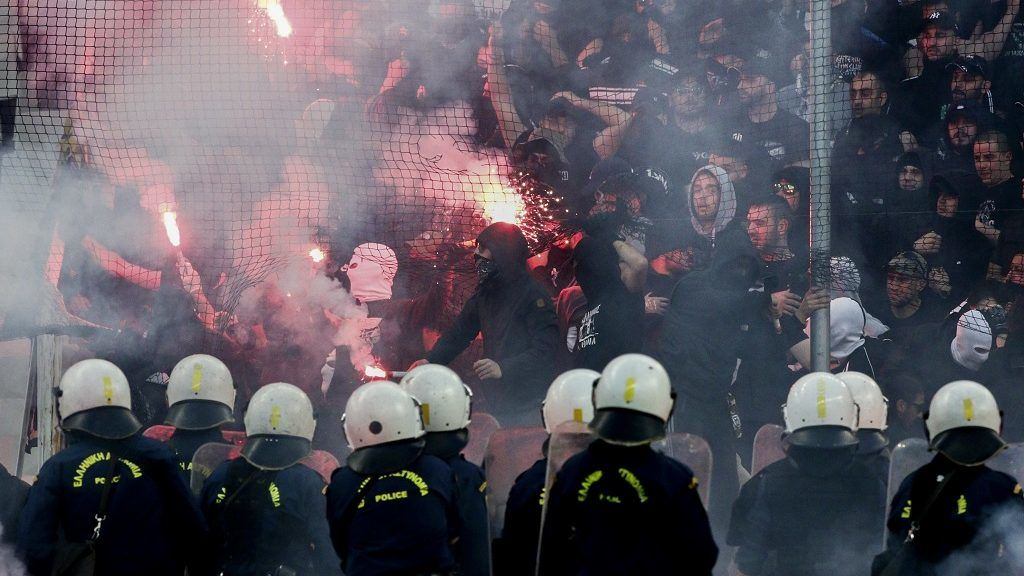 PAOK Salonika's fans throw flares towards police officers ahead of the Greek Cup Final football match between AEK FC and PAOK Salonika at the Olympic stadium in Athens on May 12, 2018. / AFP PHOTO / ANDREAS PAPAKONSTANTINOU