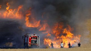 Israeli firemen attempt to put out a fire in a wheat field near the Kibbutz of Nahal Oz along the border with the Gaza Strip, on May 15, 2018 after they were started by Palestinian incendiaries during clashes with Israeli forces. Palestinians were gathering today for fresh protests along the Gaza border, a day after Israeli forces killed dozens there as the US embassy opened in Jerusalem on what was the conflict's bloodiest day in years. / AFP PHOTO / Jack GUEZ