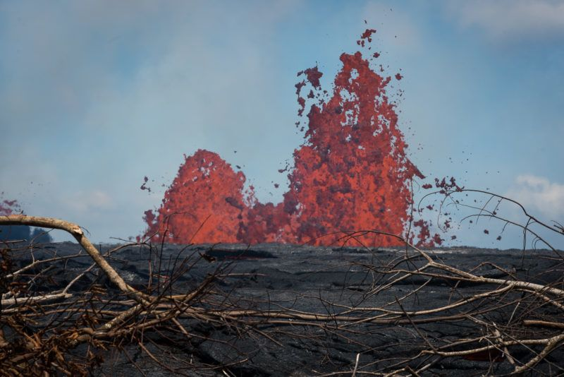 """Fissure #21 of the Kilauea volcano is seen on May 22, 2018 in the Leilani Estates subdivision of Pahoa, Hawaii.  Authorities in Hawaii have warned of dangerous """"laze"""" fumes as molten lava from the erupting Kilauea volcano reached the Pacific Ocean. Two lava flows """"reached the ocean along the southeast Puna coast overnight,"""" on Hawaii's Big Island, the US Geological Survey, which monitors volcanoes and earthquakes worldwide, said in a statement May 20, 2018. / AFP PHOTO"""