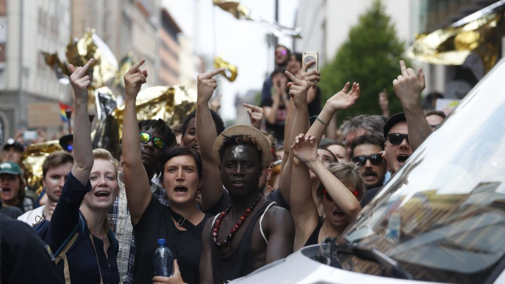 """Counter-demonstrators give their middle fingers as Alternative for Germany (AfD)'s demonstrators march in Berlin during the """"demonstration for the future of Germany"""" called by the far-right AfD in Berlin on May 27, 2018. Thousands of anti-racism campaigners, left-wingers and techno lovers are expected to pack the streets of Berlin on May 27, 2018 to protest a rally called by the far-right AfD party, with police deploying in force to keep the peace. / AFP PHOTO / Odd ANDERSEN"""