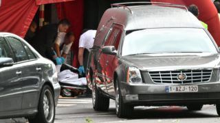 Hearses came to transport the bodies of the victims inside the security perimeter set by the police at the scene of a shooting in Liege, on May 29, 2018, after a gunman shot dead three people, two of them policemen, before being killed by elite officers.  A gunman on May 29 shot dead two female police officers with their own weapons before killing a bystander in a brazen suspected terror attack in Belgium, briefly taking a hostage at a school before being killed by police.  / AFP PHOTO / BELGA / ERIC LALMAND / Belgium OUT