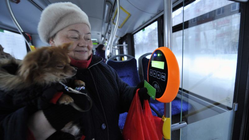 A woman holds her dog while she holds a green special card to a reading device in a bus in Tallinn, on January 9, 2013. From January 1, 2013,  residents of the Estonian capital can use public transports in Tallinn for free after purchasing a special card for 2 euros. AFP PHOTO / RAIGO PAJULA / AFP PHOTO / RAIGO PAJULA