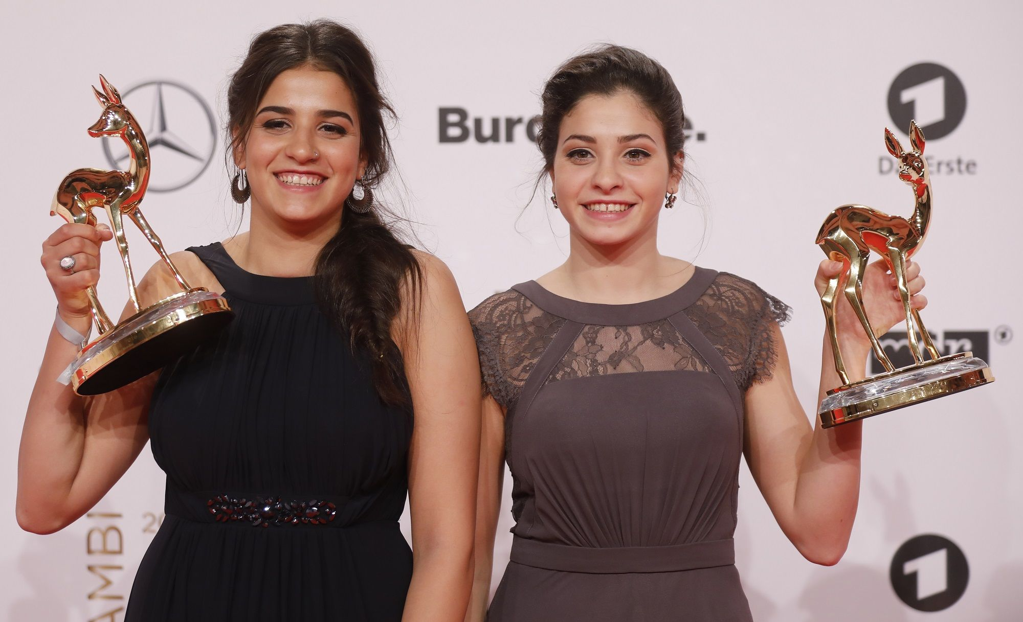 Syrian refugees and swimmers Yusra and Sarah Mardini pose for photographers with the trophy at the Bambi awards on November 17, 2016 in Berlin.  The Bambis are the main German media awards.  / AFP PHOTO / Axel SCHMIDT