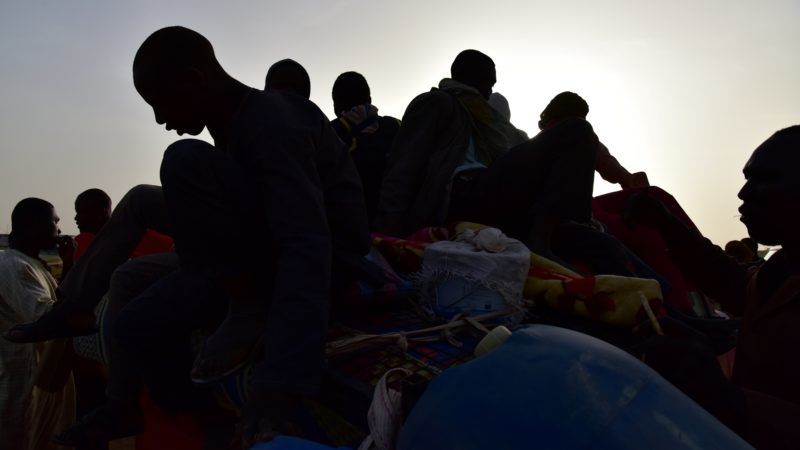 A picture taken on March 31, 2017 shows West African migrants returning from Niger after fleeing Libya due to armed groups by pickup truck in Agadez, northern Niger, following their failed attempt to reach Europe by crossing the Mediterranean Sea.  Many migrants from sub-Saharan Africa are driven through southern Libya in trucks to the northern coast where they later attempt the perilous Mediterranean crossing to Italy in Europe some 300 kilometres (180 miles) away. People traffickers have exploited the chaos in Libya since the 2011 uprising deposed and killed strongman Moamer Kadhafi to boost their lucrative but deadly trade.  / AFP PHOTO / ISSOUF SANOGO