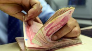 """--FILE--A Chinese clerk counts RMB (renminbi) yuan banknotes at a bank in Qionghai city, south China's Hainan province, 18 April 2018.  China's monetary authority listed steady progress to achieve completely free use of the yuan in cross-border capital investment as one of its priorities this year, based on further market-oriented exchange rate reform, said a statement released on the central bank's website on Tuesday (8 May 2018). Pan Gongsheng, vice-governor of the People's Bank of China and director of the State Administration of Foreign Exchange, called for expansion of the global use of the yuan under a """"macro prudential"""" management framework to monitor market fluctuations. These points, part of the central bank's 2018 annual work plan, were released after the nation's policymakers introduced reforms to further open the domestic financial sector to foreign investors."""