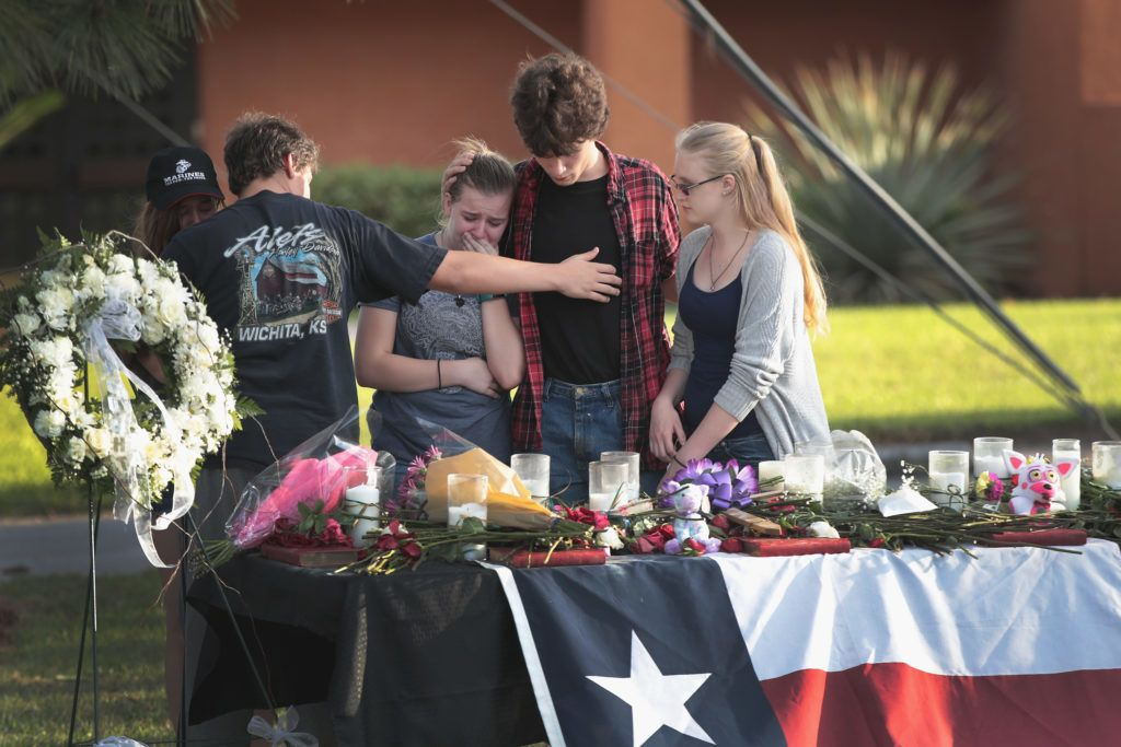 SANTA FE, TX - MAY 19: Santa Fe High School students gather at a mekeshift memorial during a community dinner put on by voluteers to help residents begin healing on May 19, 2018 in Santa Fe, Texas. Yesterday morning, 17-year-old student Dimitrios Pagourtzis entered the school with a shotgun and a pistol and opened fire, killing 10 people.   Scott Olson/Getty Images/AFP