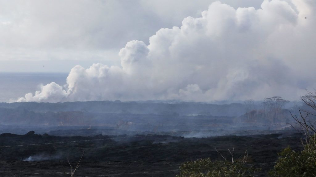 KAPOHO, HI - MAY 20: A steam plume rises (TOP) from lava entering the Pacific Ocean, after flowing to the water from a Kilauea volcano fissure, on Hawaii's Big Island on May 20, 2018 in Kapoho, Hawaii. Lava cools on land in the foreground. Officials are concerned that 'laze', a dangerous product produced when hot lava hits cool ocean water, will affect residents. Laze, a word combination of lava and haze, contains hydrochloric acid steam along with volcanic glass particles.   Mario Tama/Getty Images/AFP