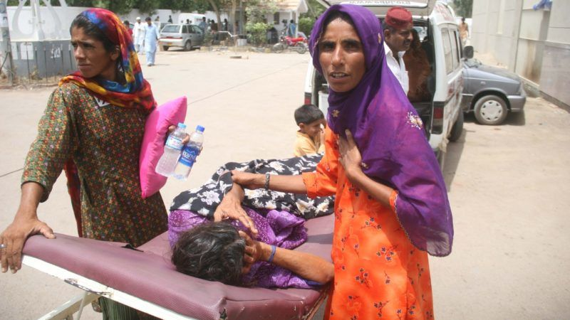 KARACHI, PAKISTAN - JULY 01: Pakistani relatives shift a heatstroke victim to a government hospital in Karachi, Pakistan, July 01, 2015. Nearly two-thirds of the victims of a killer heatwave that swept southern Pakistan last week were homeless people, a minister said as the death toll in Karachi reached over 1,200. Sabir Mazhar / Anadolu Agency