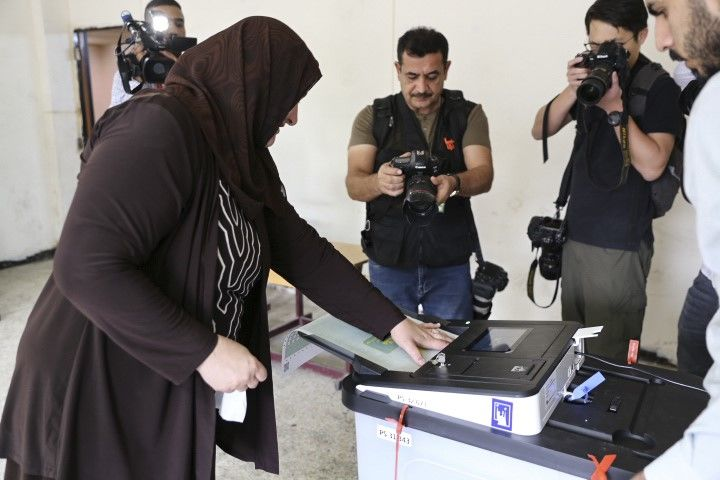 BAGHDAD, IRAQ - MAY 12: An Iraqi woman puts his ballot paper in an electronic box following casting her vote for the Iraqi parliamentary election at the Al Messere Primary School in Baghdad, Iraq on May 12, 2018. Visam Ziyad Muhammed / Anadolu Agency