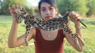 Ah Lin Tuch cooking and eating the endangered fishing cat.NEWS COPY - WITH VIDEO AND PICTURESA woman was arrested after she filmed herself cooking and EATING endangered animals - to earn money on YOUTUBE.Mother-of-one Ah Lin Tuch and husband Phoun Raty made videos of her skinning an endangered fishing cat, a large lizard and protected species of birds.Wearing hot pants and crop tops, she grilled them on a camp fire fire and ate them in the jungle near the home in Phnom Penh, Cambodia. Other clips show her eating a king cobra, shark, sting ray and frogs.But the footage sparked fury from viewers who slammed the would-be survivalist when it emerged that the many of the creatures were protected species. The country's Ministry of Environment launched a man hunt for the couple last Wednesday (09/05) and the next day they appeared before the public admitting they cooked the animals and apologising for ''destroying our wild life''.Chea Sam Arng, head of the Environment Ministry's General Directorate for Administration of Nature Conservation and Protection, said: ''We are now in the process of taking legal action against them while the working group is preparing a report on the matter.