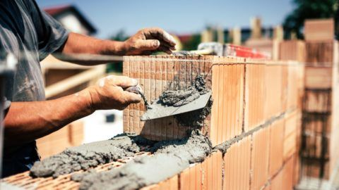 Industrial construction worker using spatula and trowel for building walls with bricks and mortar
