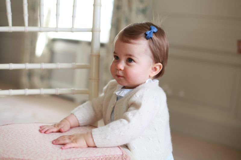 ANMER HALL, ENGLAND - APRIL 2016:  In this undated handout photo provided by HRH The Duke and Duchess of Cambridge released on May 1, 2016, Princess Charlotte of Cambridge looks up with her hands placed on a chair as her mother Catherine, Duchess of Cambridge takes her photo ahead of her first birthday on May 2, 2016 at Anmer Hall on April 2016 in Norfolk, England. The young Princess will celebrate her first birthday on May 2. (Photo by HRH The Duchess of Cambridge via Getty mages) EDITORIAL USE ONLY. NO COMMERCIAL USE (including any use in merchandising, advertising or any other non-editorial use including, for example, calendars, books and supplements). This photograph is provided to you strictly on condition that you will make no charge for the supply, release or publication of it and that these conditions and restrictions will apply (and that you will pass these on) to any organisation to whom you supply it. All other requests for use should be directed to the Press Office at Kensington Palace in writing.