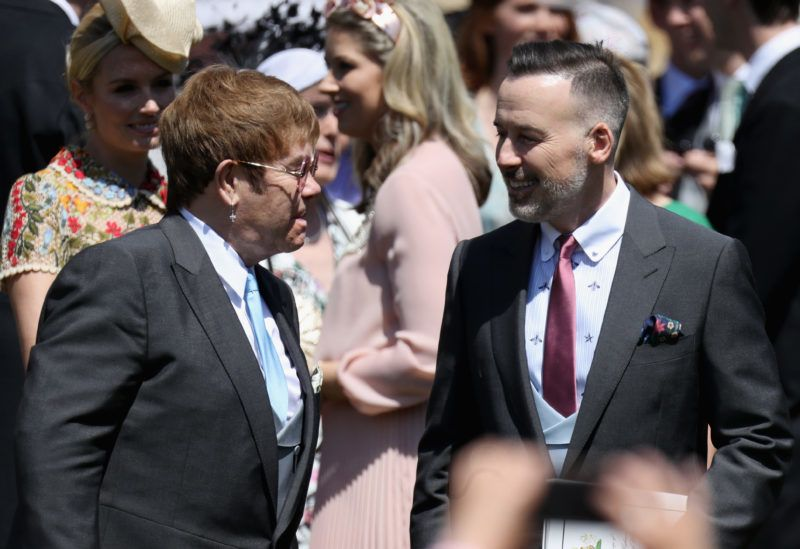 WINDSOR, ENGLAND - MAY 19: Sir Elton John and David Furnish (R) arrive at the wedding of Prince Harry to Ms Meghan Markle at St George's Chapel, Windsor Castle on May 19, 2018 in Windsor, England. Prince Henry Charles Albert David of Wales marries Ms. Meghan Markle in a service at St George's Chapel inside the grounds of Windsor Castle. Among the guests were 2200 members of the public, the royal family and Ms. Markle's Mother Doria Ragland.  (Photo by Chris Jackson/Getty Images)