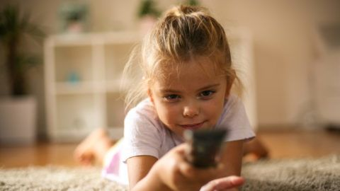 Little girl lying on floor and changing TV channel with remote.