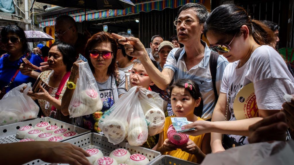 "Customers buy traditional buns made for the annual Cheung Chau bun festival in Hong Kong on May 3, 2017. Tens of thousands gathered in Hong Kong on May 3 for one of its most colourful festivals, a whirlwind of music and costume culminating in a dramatic climb up a precipitous ""bun tower"". / AFP PHOTO / Anthony WALLACE"