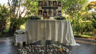 """A poster showing cabin crew from missing Malaysia Airlines flight MH370 is displayed during a prayer at a school in Petaling Jaya on March 8, 2016.  Malaysia and Australia said they remained """"hopeful"""" of solving the mystery of flight MH370 as the second anniversary of the plane's disappearance arrived on March 8 with no end in sight for devastated families. / AFP PHOTO / MOHD RASFAN"""