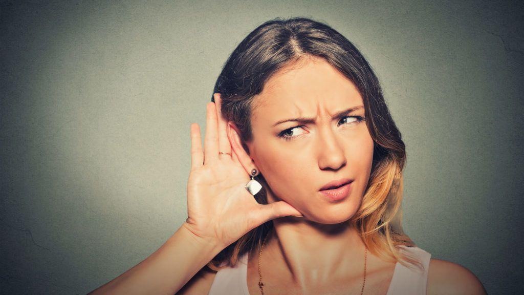 Closeup portrait concerned young nosy woman hand to ear gesture carefully intently secretly listening juicy gossip conversation news isolated grey background. Human face expression. Privacy violation