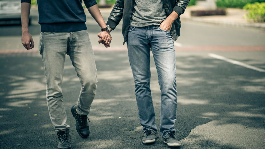 Cropped image of gay couple holding hands