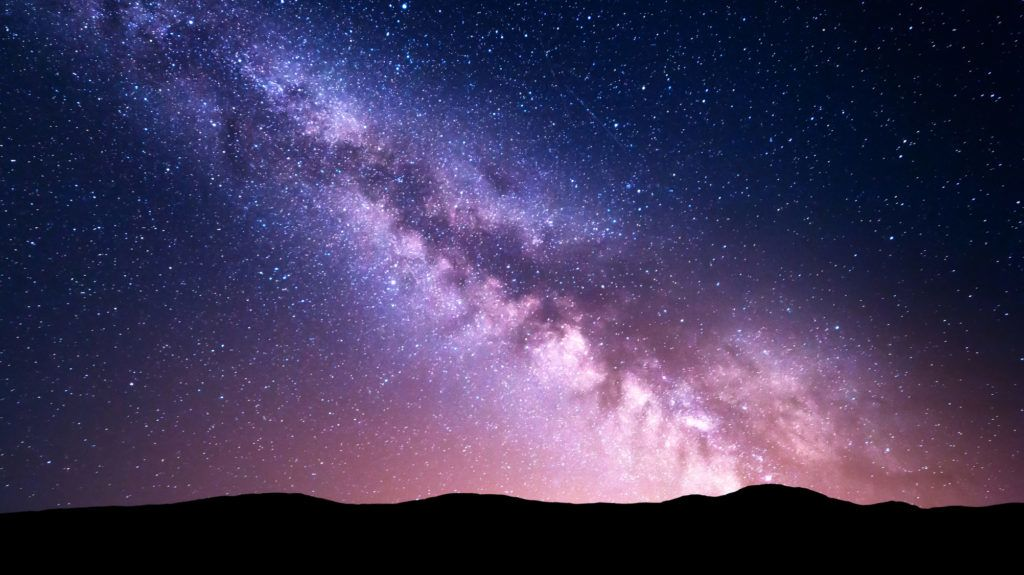 Night landscape with vibrant Milky Way at mountains. Starry sky with hills at summer. Beautiful Universe. Space background. Night sky with Milky Way