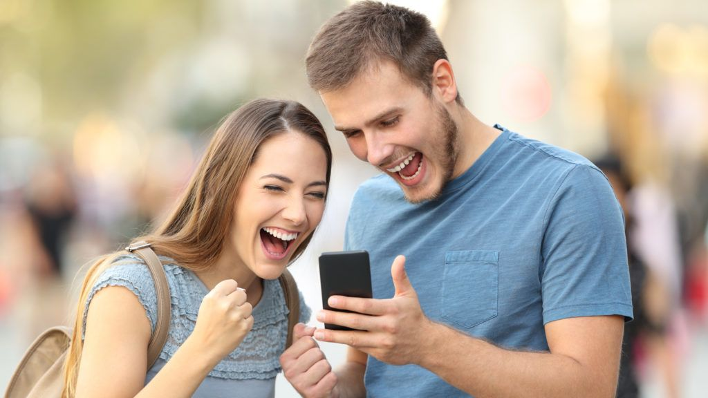 Excited couple receiving good news on line in a smart phone outside on the street