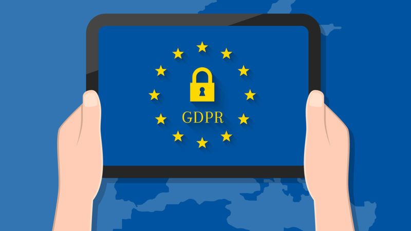 GDPR concept. Hand holding tablet with lock symbol and European Union flag on its screen display.