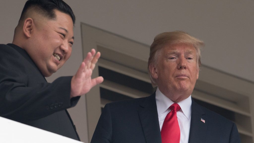 North Korea's leader Kim Jong Un (L) waves as he and US President Donald Trump look on from a veranda during their historic US-North Korea summit, at the Capella Hotel on Sentosa island in Singapore on June 12, 2018. Donald Trump and Kim Jong Un have become on June 12 the first sitting US and North Korean leaders to meet, shake hands and negotiate to end a decades-old nuclear stand-off. / AFP PHOTO / SAUL LOEB
