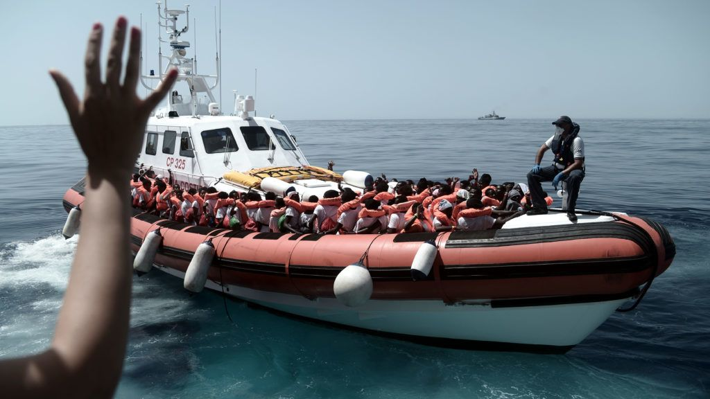 """This handout picture obtained from the French non-governmental organisation Medecins Sans Frontiers - Doctors Without Borders(MSF)/SOS Mediterranee on June 13, 2018 shows rescued migrants and MSF personnel onboard an Italian coastguard ship following their transfer from the French NGO's ship Aquarius.  An Italian coastguard ship carrying more than 900 migrants was allowed to dock in Sicily, after Italy controversially turned away a separate foreign vessel with rescued migrants on board. / AFP PHOTO / MSF/SOS MEDITERRANEE / Karpov / RESTRICTED TO EDITORIAL USE - MANDATORY CREDIT """"AFP PHOTO / MSF/SOS Mediterranee / KARPOV"""" - NO MARKETING NO ADVERTISING CAMPAIGNS - DISTRIBUTED AS A SERVICE TO CLIENTS == NO ARCHIVE"""