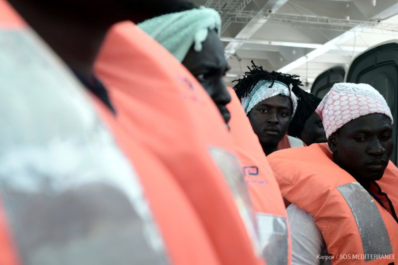 """This handout picture obtained from French non-governmental organisations Medecins Sans Frontiers - Doctors Without Borders (MSF) and SOS Mediterranee on June 14, 2018 shows migrants wearing life jackets. French rescue boat Aquarius carrying migrants is on June 14, 2018 on its way to Spain. The NGO vessel became the centre of an ugly European row after being turned away by Italy and Malta, until Spain said on June 11 the ship could land at the port of Valencia, where it is expected to arrive late on June 16. / AFP PHOTO / SOS MEDITERRANEE / Kenny Karpov / RESTRICTED TO EDITORIAL USE - MANDATORY CREDIT """"AFP PHOTO / SOS MEDITERRANEE / KENNY KARPOV"""" - NO MARKETING NO ADVERTISING CAMPAIGNS - DISTRIBUTED AS A SERVICE TO CLIENTS"""