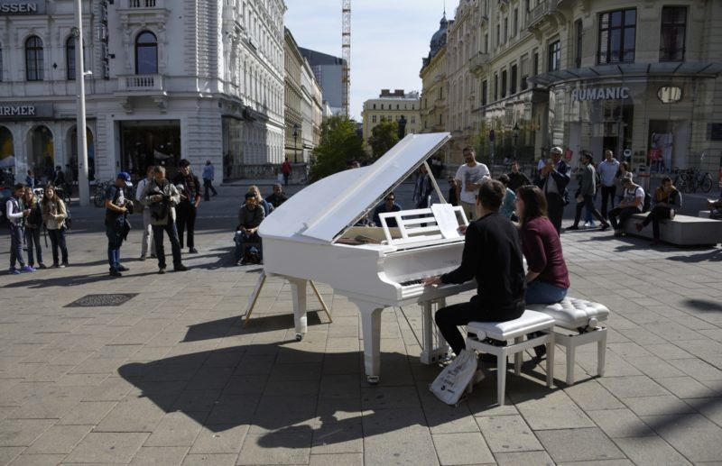 Austrian students Mariella and Claus (L) sing and play a piano in the city centre of Vienna on September 23, 2016 in Vienna, Austria. Open Piano For Refugees is a project sponsored by Klavierhouse Fiedler & Sohn which allows visitors and passersby to play their piano, listen and donate money to help refugees. / AFP PHOTO / JOE KLAMAR