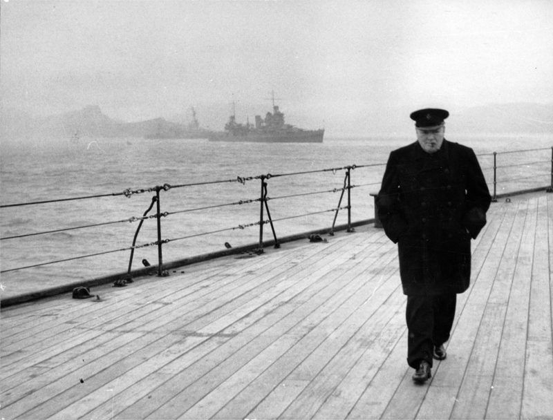 """World War II (Second World War) : Winston Spencer Churchill (1874-1965) British statesman, in overcoat and hat and smoking a cigar, walking alone on the deck of HMS """"Prince of Wales"""" during the Atlantic Conference in 1941. World History Archive"""