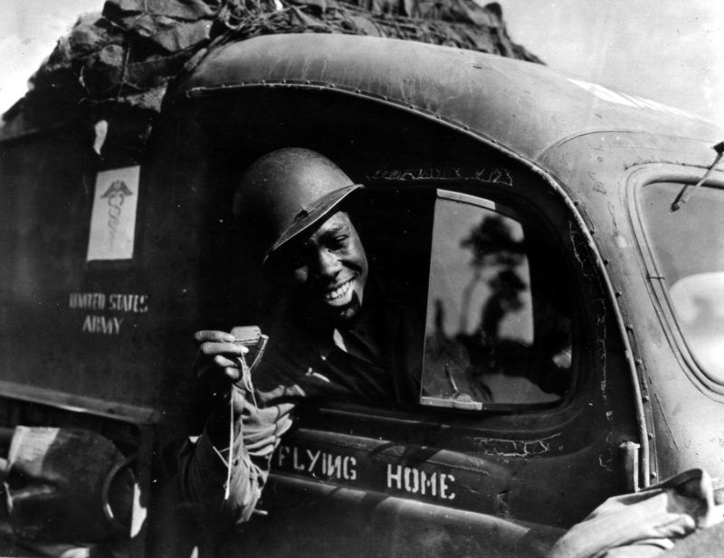 A U.S Black ambulance driver exhibits a 50-caliber machine gun bullet which lodged just above the windshield of his vehicle when he was strafed by a German plane while driving at the front somewhere in France (Summer 1944) Photos12.com - Coll-DITE - USIS