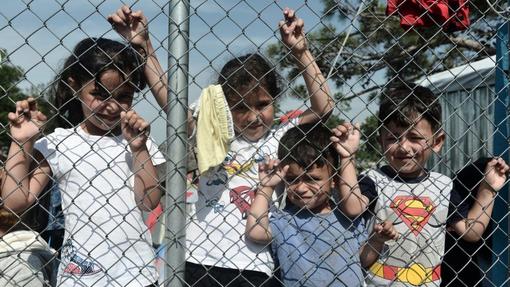 Migrants and refugee children who live in a camp in a suburb west of the northern city of Thessaloniki stand behind a fence as adult (unseen) hold a protest to highlight their poor living conditions on May 23, 2018.  Greece, a country of 11 million people, recorded 58,661 asylum applications last year, making it the member state with the highest number of asylum seekers per capita, according to official data. / AFP PHOTO / Sakis MITROLIDIS