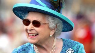 (FILES) In this file photo taken on May 31, 2018 Britain's Queen Elizabeth II arrives for a garden party at Buckingham Palace in London. Britain's 92-year-old Queen Elizabeth II underwent eye surgery to remove a cataract in May, Buckingham Palace said on June 8, 2018. In recent weeks the monarch has been seen wearing sunglasses at a number of events including the Royal Windsor Horse Show and Buckingham Palace garden parties. Normally an impeccable observer of decorum, it is thought the Queen donned the shades on the advice of doctors whilst one eye recovers from surgery to replace the cloudy lens with an artificial one.   / AFP PHOTO / POOL / Yui Mok