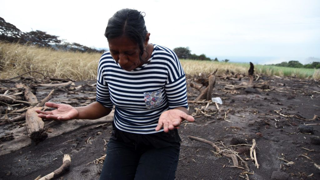 Eufemia Garcia prays before searching for relatives, victims of the Fuego Volcano in the ash-covered village of San Miguel Los Lotes, in Escuintla department, about 35 km southwest of Guatemala City, on June 8, 2018. The threat of fresh landslides forced emergency workers Thursday to suspend a search for victims of a major eruption of Guatemala's Fuego Volcano, the country's disaster management agency said. To date, 109 people are known to have died in Sunday's eruption, with nearly 200 still reported as missing. / AFP PHOTO / ORLANDO ESTRADA
