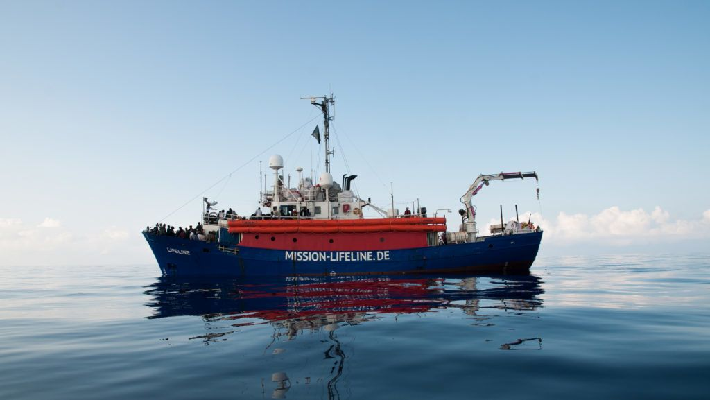 """This handout picture obtained on June 22, 2018 from the German NGO 'Mission Lifeline' shows migrants onboard the Lifeline sea rescue boat at sea on June 21, 2018. Italy said on June 21, 2018 that it would seize two rescue migrant ships, one of which is stranded in the Mediterranean carrying over 200 migrants, adding that they were """"illegally"""" flying the Dutch flag. The ships Lifeline and Seefuchs, of the German NGO Mission Lifeline and Sea Eye, """"will be seized by the Italian government and directed into our ports"""" to launch an investigation into their legal status, announced Italy's infrastructure minister Danilo Toninelli. The announcement comes after Italy's new populist government earlier this month refused to take in the Aquarius rescue ship, carrying some 630 migrants, sparking an EU migration row.  / AFP PHOTO / Mission Lifeline / Hermine POSCHMANN / RESTRICTED TO EDITORIAL USE - MANDATORY CREDIT """"AFP PHOTO /  MISSION LIFELINE """" - NO MARKETING NO ADVERTISING CAMPAIGNS - DISTRIBUTED AS A SERVICE TO CLIENTS"""