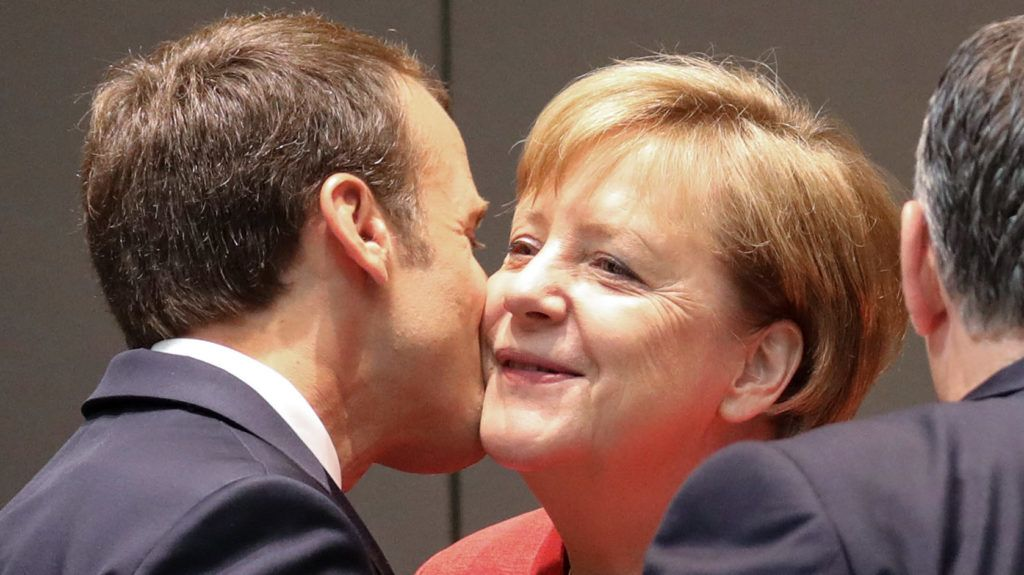"""France's President Emmanuel Macron (L) kisses Germany's Chancellor Angela Merkel during the last day of the European Union leaders' summit, without Britain, to discuss Brexit and eurozone reforms on June 29, 2018 at the Europa building in Brussels. EU leaders clinched a hard-won migration deal during all-night talks on June 29, that Italy's hardline new premier said meant his country was """"no longer alone"""" in shouldering the responsibility for migrants. / AFP PHOTO / Ludovic MARIN"""