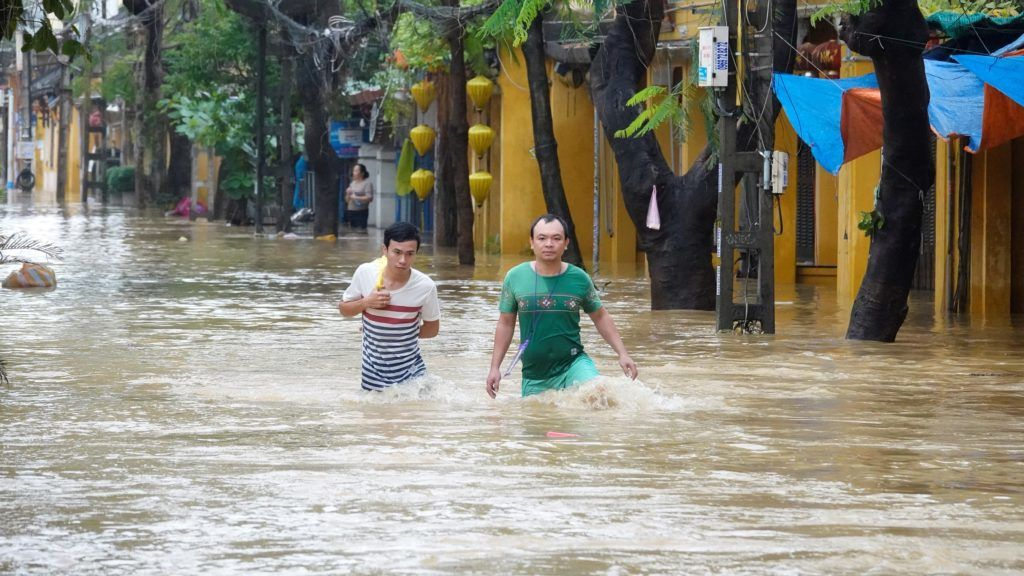 Local residents wade through flood waters at the central tourist town of Hoi An on November 6, 2017 following havy rains caused by Typhoon Damrey landed on central Vietnam.  At least 44 people have died after Typhoon Damrey slammed into central Vietnam, disaster officials said with several areas totally submerged in the worst flooding in years. / AFP PHOTO / STR