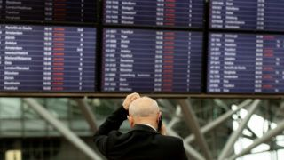 dpatop - 03 June 2018, Germany, Hamburg: A man is on the phone while standing in front of the flight information boards at Hamburg Airport. Hamburg Airport suspended its operation after a blackout. Photo: Daniel Reinhardt/dpa