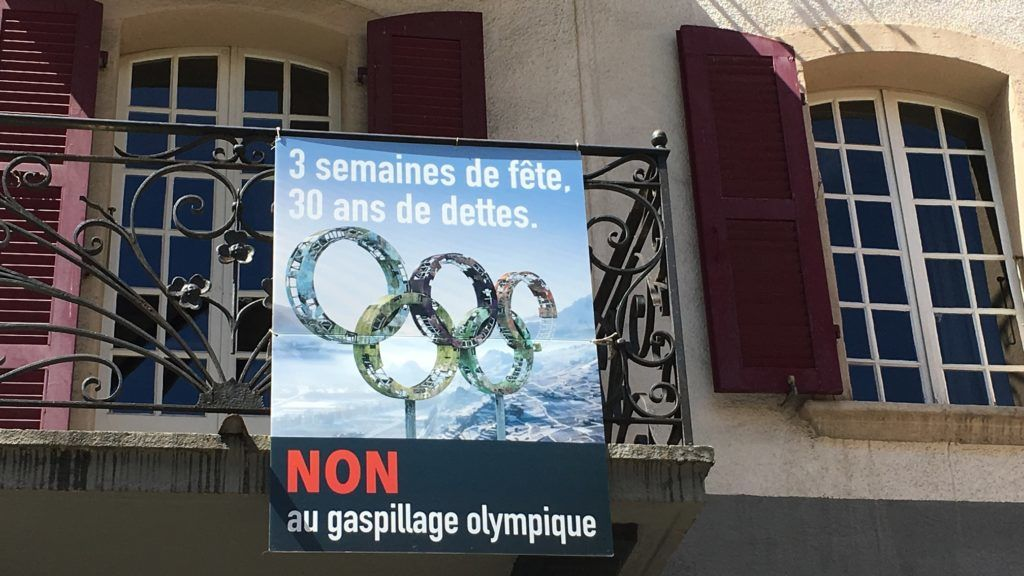 """FILED - 14 May 2018, Switzerland, Sion: A poster of opponents of an application for the 2026 Olympic Games hangs on a balcony. """"3 weeks hard and 30 years debt"""" is it. Olympia in the Alps - the Swiss city of Sion wants to host 2026 games of the new kind, without expensive buildings, very sustainable. The opponents of the plans are suspicious after the experience of the winter games in South Korea and Russia. On Sunday will be voted. Photo: Christiane Oelrich/dpa"""