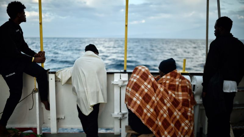 """(FILES) In this file photo taken on May 14, 2018 migrants look at the coastline as they stand aboard the French rescue ship MV Aquarius, off the coast of Sicily.  Hundreds of people on board the French NGO's ship Aquarius, a search and rescue ship run in partnership between """"SOS Mediterranee"""" and Doctors without borders (MSF), were stranded on June 11, 2018 in the Mediterranean between Italy and Malta in a standoff between the two nations, with both refusing to allow the vessel to dock. Some 629 people, including pregnant women and scores of children, have been saved by SOS Mediterranee on June 10 and embarked aboard the French NGO's ship, between Malta and Sicily waiting for a secure port. / AFP PHOTO / LOUISA GOULIAMAKI"""