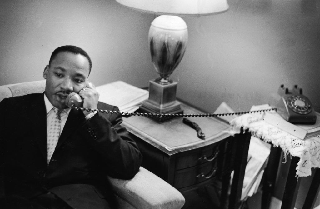 American civil rights leader Dr. Martin Luther King, Jr. (1929 - 1968) sits on a couch and speaks on the telephone after encountering a white mob protesting against the Freedom Riders in Montgomery, Alabama, May 26, 1961. (Photo by Express Newspapers/Getty Images)