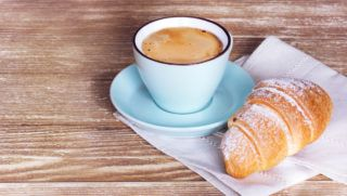 Coffee croissant on wooden table background empty copy space.French breackfast.