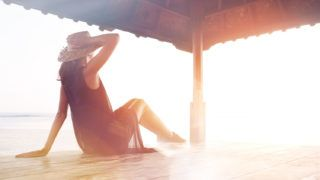 Young pretty woman relaxing near ocean. Blurred effect, lens flares effect, intentional sun glare