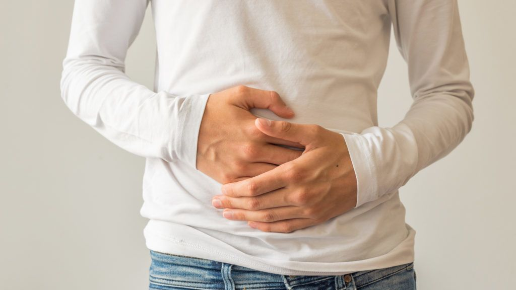 Young man suffering from stomach ache, diarrhea, constipation, acid reflux, indigestion, nausea