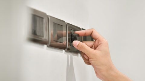 Close up hand turning on grey light dimmer switch. Copy space.